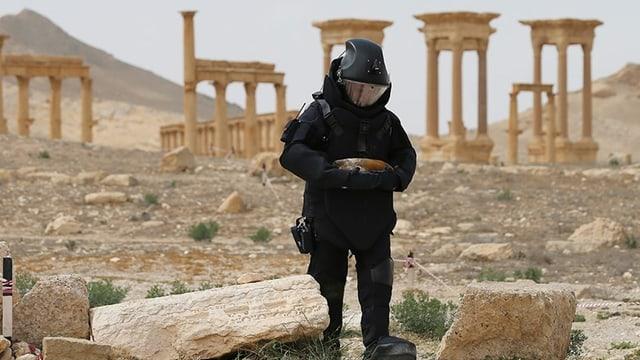 Mann in schwarzer Uniform vor Tempel.