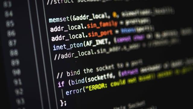 Bildschirm mit Programmier-Quellcode auf schwarzem Hintergrund