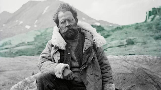 Alfred de Quervain sitzt auf einem Felsen. Er ist in Gronländ.