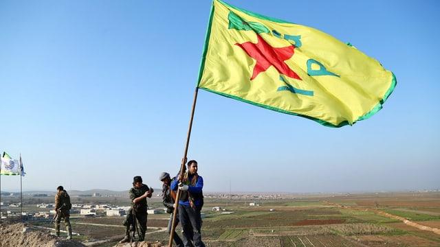 Kurdische Kämpfer hissen eine Fahne bei Kobane