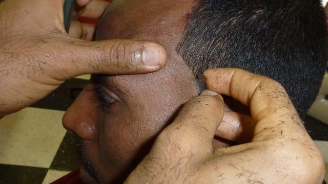 Grond: Il maun da Samuel Jambo, che tegn ina nezza da far la barba el maun blut. Cun quella taglia el la contura dals chavels sper la tempra dal model.