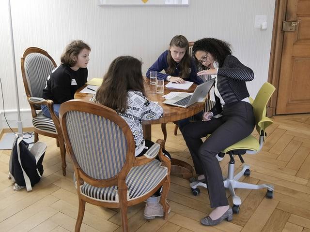 Die Aargauer Staatsschreiberin sitzt an einem Tisch mit drei Mädchen.