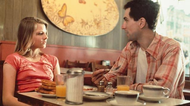 Mann und Frau sitzen am Tisch und reden miteinander