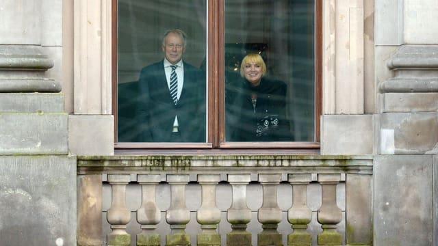 Grünen-Chefin Claudia Roth und ihr Parteikollege Jürgen Trittin hinter einer Fensterscheibe.