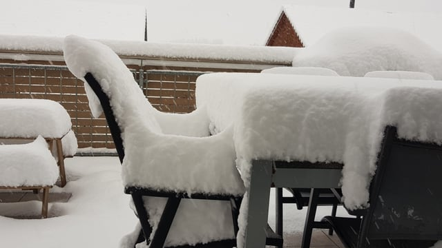 Gartenmöbel auf einer Terrasse. Mit 20 Centimetern Schnee bedeckt.