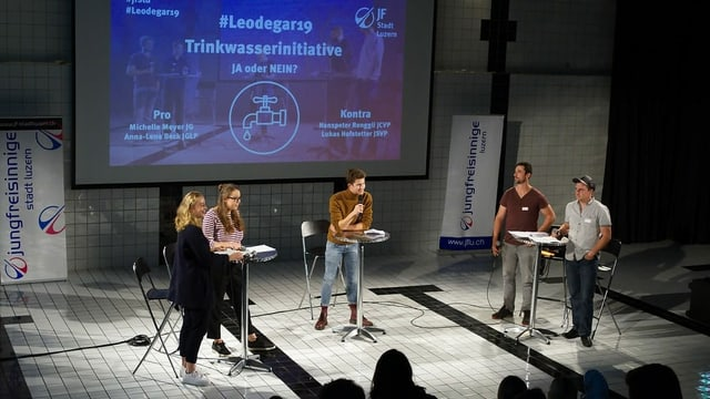 Fünf Leute auf einer Bühne an Stehpulten am diskutieren.