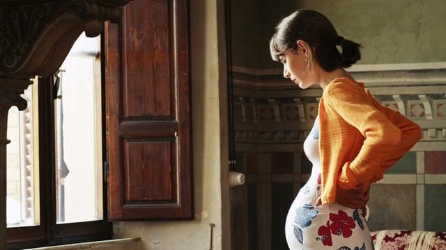 Schwangere Frau steht vor Fenster