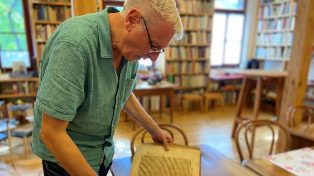 Antiquar Gerhard Becker blättert in der Buchhandlung in seinem Lieblingsbuch.