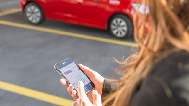 Frau hält neben Parkplatz ein Handy in der Hand