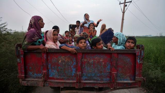 Frauen und Kinder auf einem Anhänger, fotografiert von hinten.