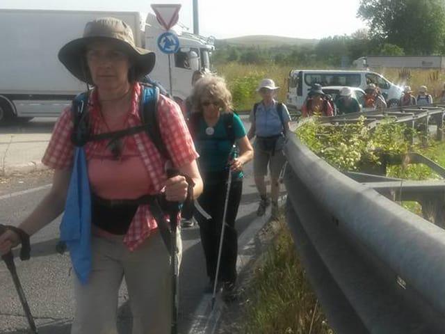 Pilgerinnen laufen neben einer Hauptstrasse.