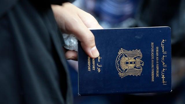 Eine Frau mit einem syrischen Pass in der Hand