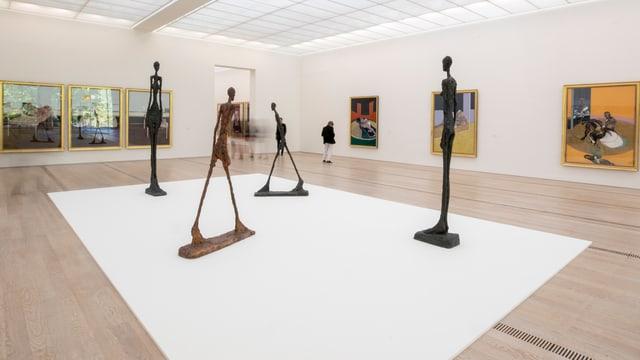 """Blick in den Raum mit den Bronze-Skulpturen von Giaccometti """"L Homme qui marche"""" sowie Gemälde von Bacon."""
