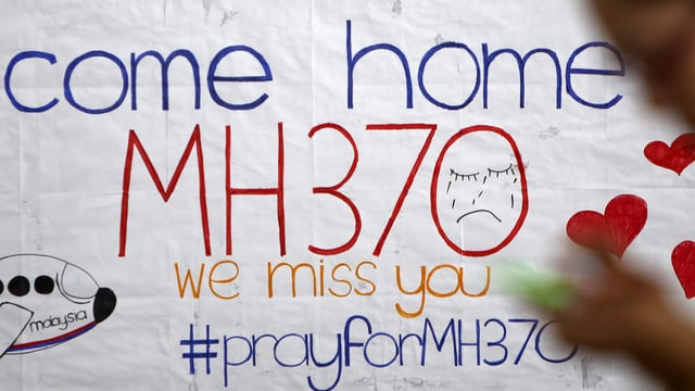 """Angehörige geben an einer Pinwand ihren Gefühlen Ausdruck, """"Come home MH3702, haben sie geschrieben"""