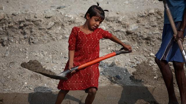 Ein kleines Mädchen in Indien schaufelt Sand.