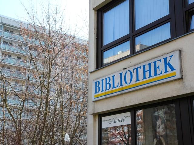 Schild an Plattenbau, daruf steht Bibliothek.