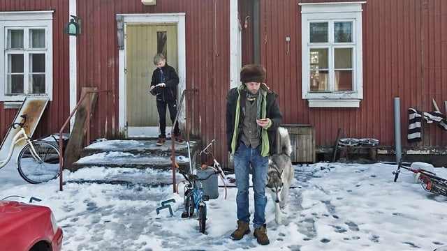 Mann in Fellmütze vor einem Haus, es liegt Schnee.