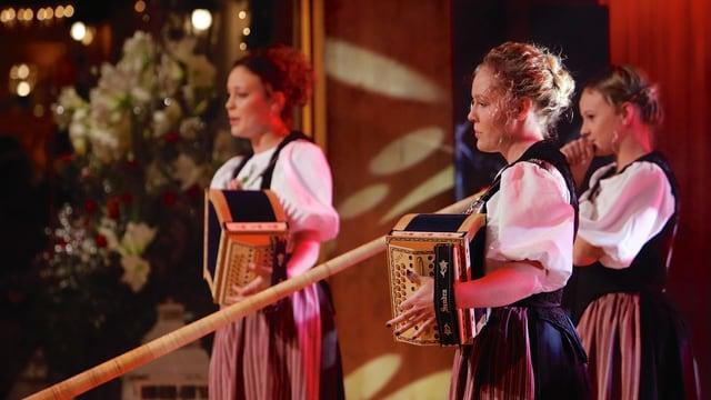 Doris mit Schwyzerörgeli, Maya mit Alphorn und Sandra mit Schwyzerörgeli auf der Bühne.