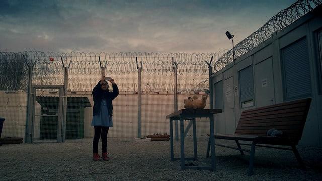 Ein Mädchen fotografiert über einen grossen Stacheldrahtzaun.