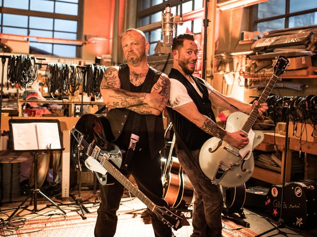 Göla und Marc Trauffer posieren mit ihren Gitarren.