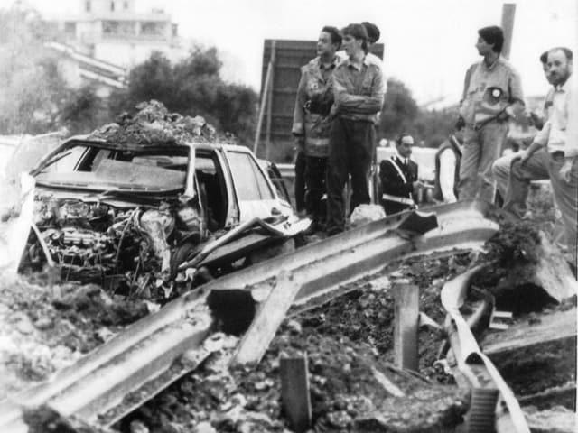 Das komplett zerstörte Auto auf der zerbröckelten Autobahn und fassungslose Leute, die daneben stehen.