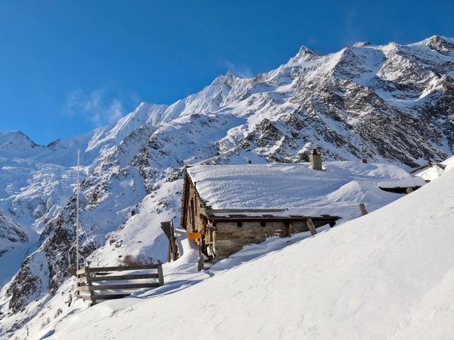 Blick auf eine verschneite Berghütte.