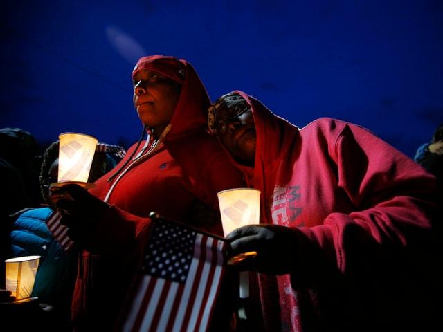 Zwei Frauen mit Kerzern und US-Fähnchen.