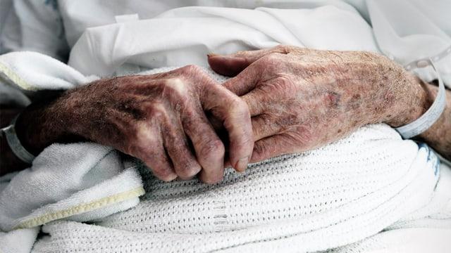 Uralte Hände, über den Decken eines Spitalbetts verschränkt