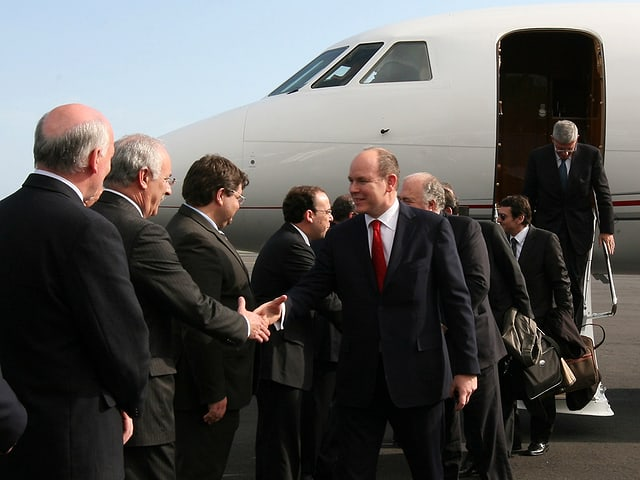 Fürst Albert von Monaco mit anderen Personen vor einem Jet.