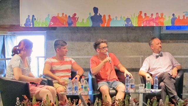 Drei Schüler und ein Mann mit Fliege sitzen auf einem Gesprächspodium, im Hintergrund SRG-Plakat.