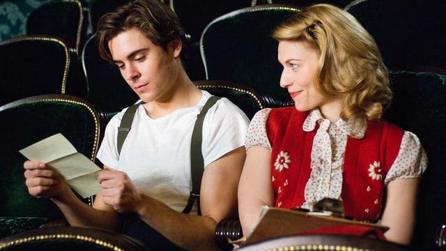 Ein Mann und eine Frau sitzen in den Stuhlreihen eines Theaters und studieren eine Notiz.