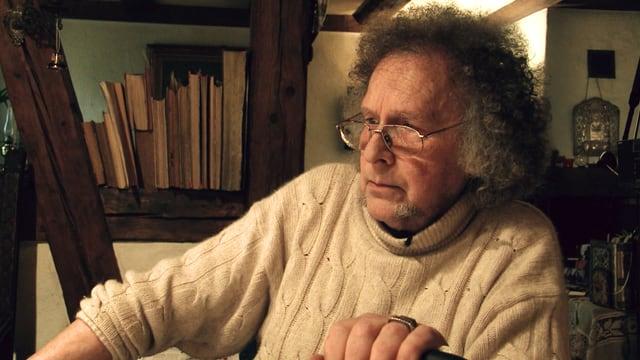 Alter Mann mit Wollpulli schaut traurig nach unten