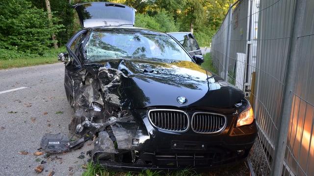 Ein zerstörter BMW-Kombi steht neben der Strasse, an ein Absperrgitter gedrückt.