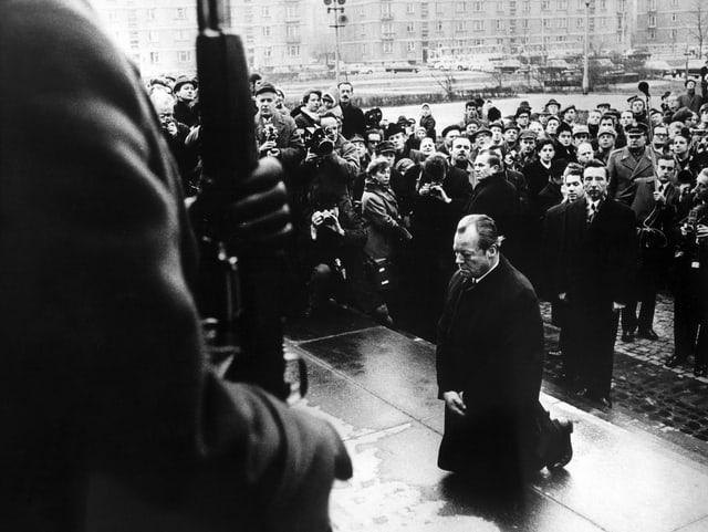 Schwarzweissbild, Willy Brandt kniet in Polen vor dem Ehrenmal der Toten des Warschauer Ghettos nieder.