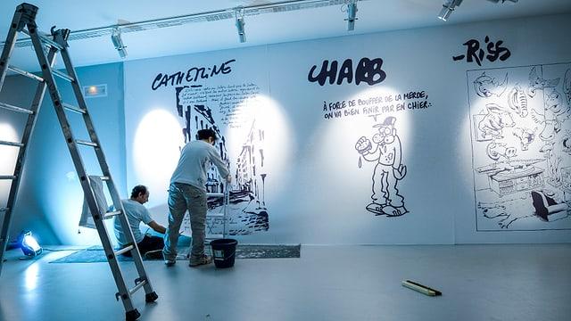 Ein paar Leute bauen an der Charlie-Hebdo-Ausstellung.