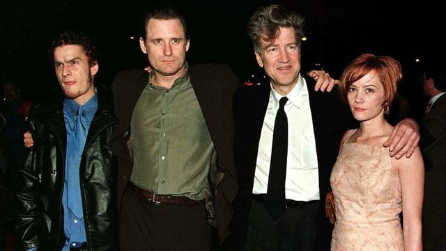 Die drei Schauspieler und David Lynch posieren Schulter an Schulter für die Kamera.