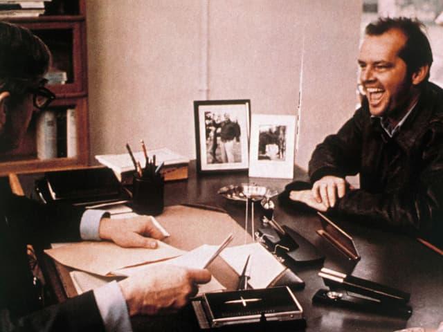 Jack alias McMurphy strahlt den psychologischen Leiter der Irrenanstalt an.