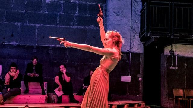 Eine Frau auf der Bühne mit 2 Revolvern in der Hand.