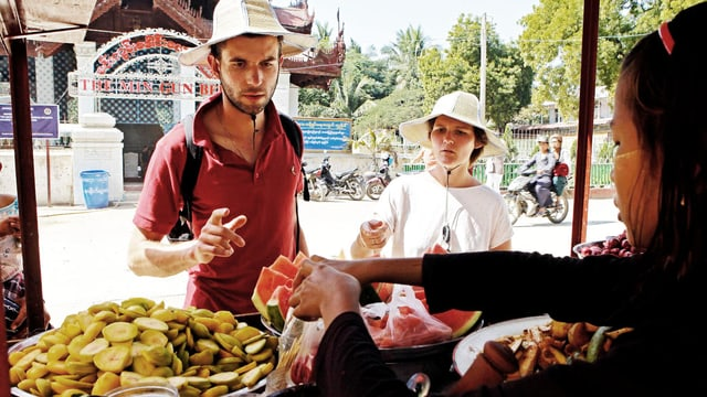 Ein junges Touristenpaar kauft an einem asiatischen Obststand ein.