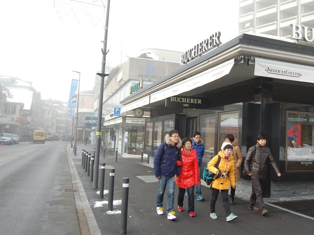 Asiatische Touristengruppe flaniert durch Interlaken