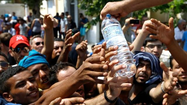 Flüchtlinge strecken ihre Hände nach einer Wasserflasche aus