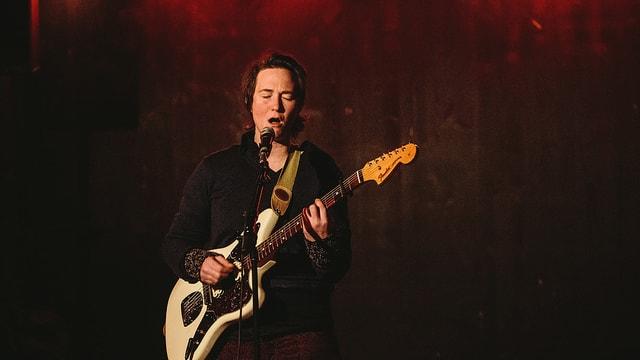 Eine Frau steht auf einer Bühne und spielt Gitarre und singt dazu.