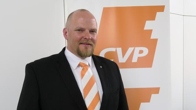 Ein Mann in Anzug und orangener Kravatte.
