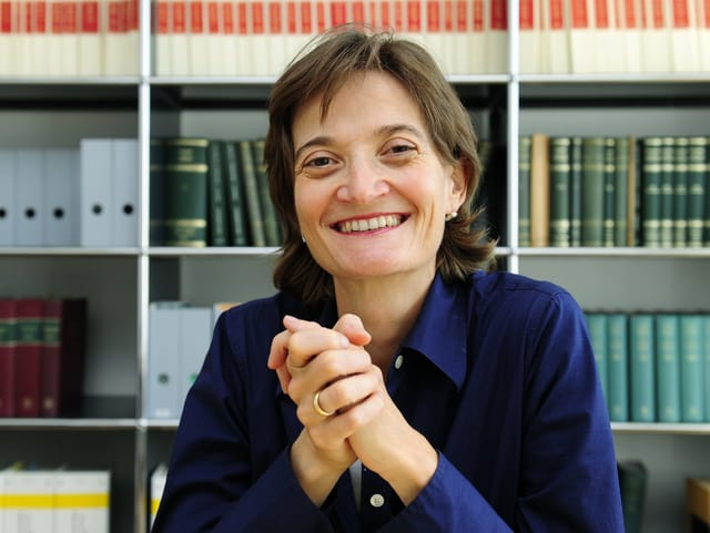 Frau mit schulterlangen braunen Haaren und blauer Bluse sitzt vor einem Bücherregal.