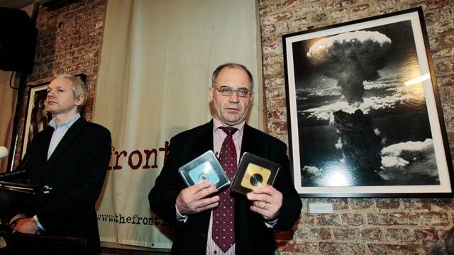 Elmer mit zwei Datenträgern in der Hand, an der Wand neben ihm das Bild einer Atomexplosion, an seiner Seite Wikileaks-Gründer Julian Assange