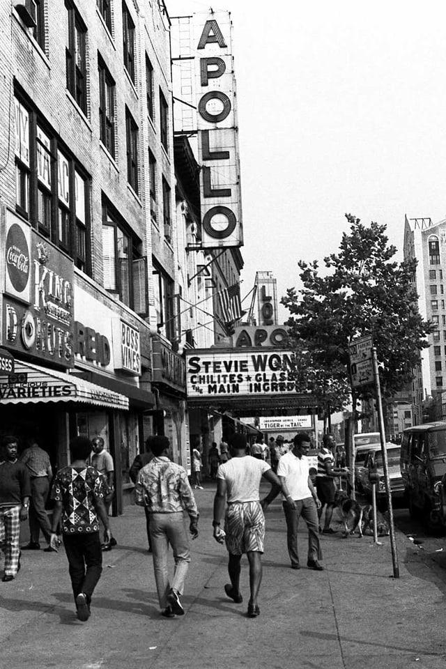 Junge Leute spazieren vor dem Apollo Theater im New Yorker Stadtteil Harlem.