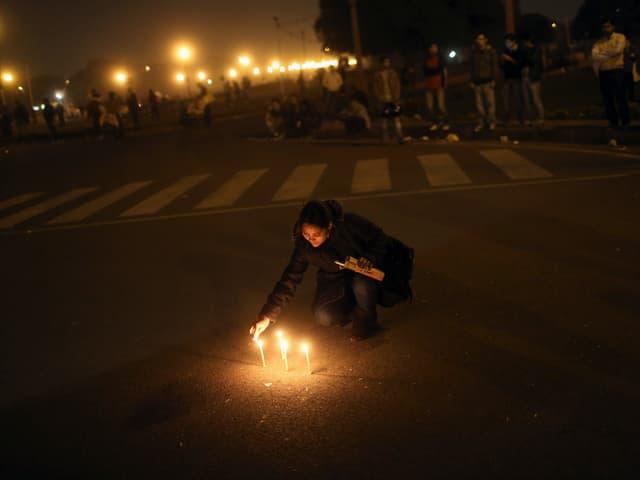 Eine Frau zündet auf einer Strasse Kerzen an