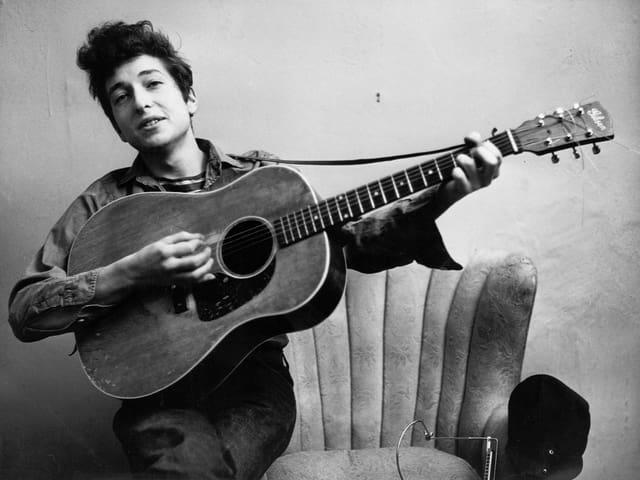 Ein Porträt von Bob Dylan mit Gitarre in der Hand.
