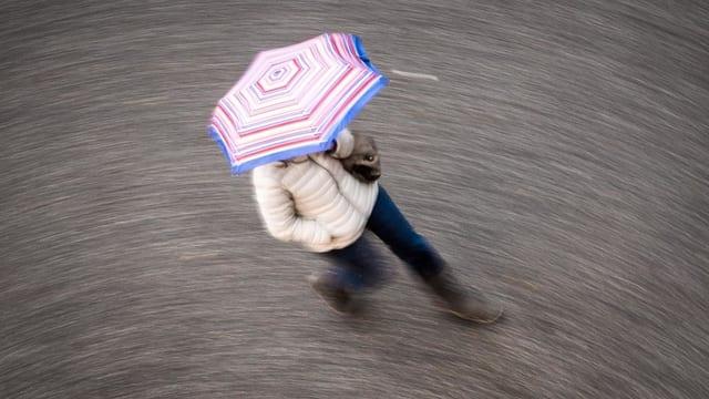 Frau mit Regenschrim geht über die Strasse.