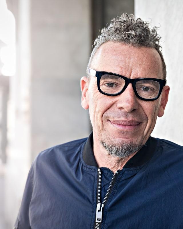 Autor Tom Kummer mit schwarz umrandeter Brille und dunkler Bomberjacke.